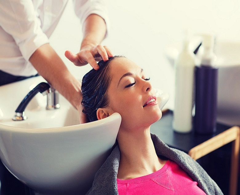 beauty and people concept - happy young woman with hairdresser w